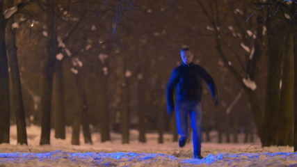 Man running at night park by trees and cars on the background