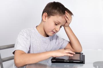 Мальчик за столом над планшетом по