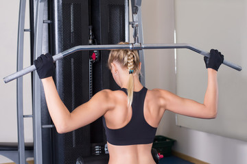Back muscles exercise by athletic woman