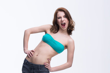 Young beautiful woman screaming over gray background