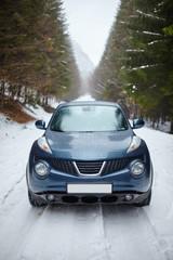 Blue car on snowy road, wintertime