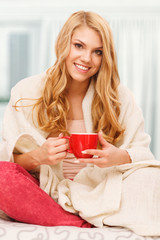 Young woman relaxing in bed with a cup of coffee