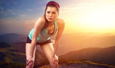 Exhausted female runner on mountain top