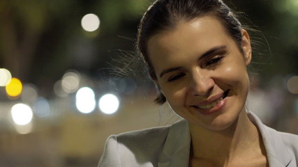 Portrait of happy, pretty woman in city at night