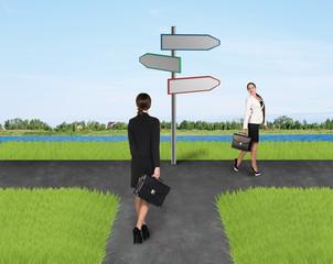 Two businesswomen near  road sign