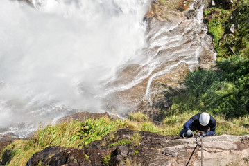 Man climbing on a via ferrata near a waterfall, Otztal, Austria