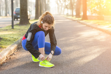 Young Sporty Woman Doing Up her Shoes Before Running.