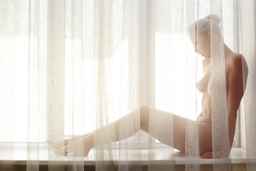 View through transparent curtain of naked woman