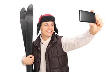 Young guy taking a selfie with his skis