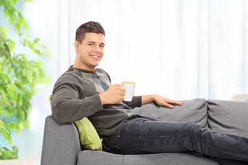 Man drinking coffee seated on sofa at home