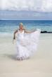 beautiful woman runs on the edge of sea on a beach. Polynesia...