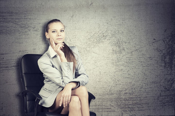 Businesswoman in office chair, looking at camera