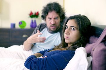 Angry husband shouting to wife in bed not listening