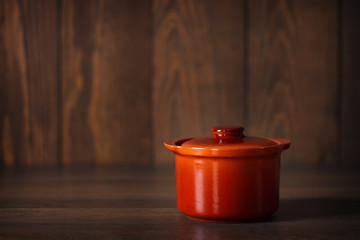 Clay pot for cooking on a wooden surface.