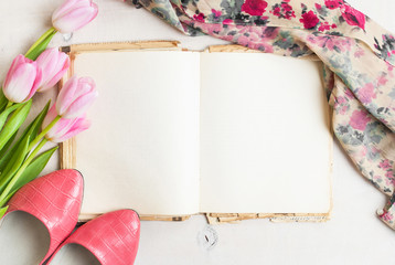 Pink tulips and blank book with women`s shoes over white wooden