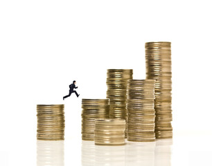 Businessman jumps over coin stacks