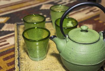 Tetera de metal verde con vasos de cristal