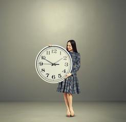 smiley woman looking at big white clock