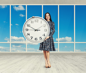 woman holding big clock, smiling