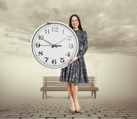 woman holding big white clock