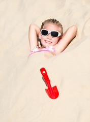 Happy cute little girl lying in sand