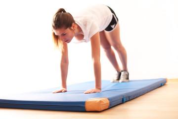 Frau macht Übungen auf Turnmatte
