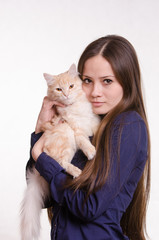 The girl is holding a red cat