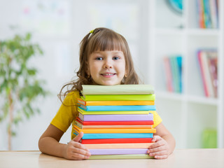 Happy kid girl with a stack of books