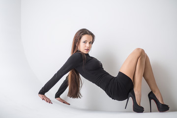 Attractive brunette in a short black dress, sitting on the floor