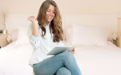 Young woman using tablet on her bedroom