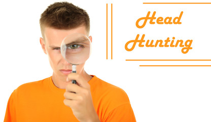 Young man looking through magnifying glass isolated