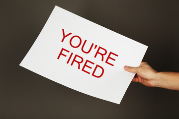 Sheet of paper with text You're Fired in male hand