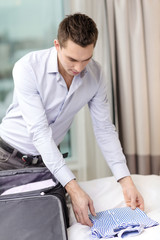 businessman packing things in suitcase