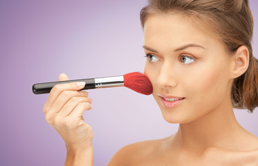 close up of young woman with makeup brush