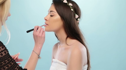 Beautiful young woman having her makeup done