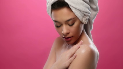 Woman applying cream on shoulder