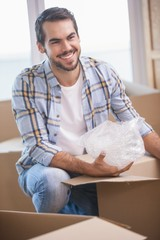 Smiling man unpacking cardboard boxes