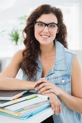Smiling businesswoman leaning on notebooks