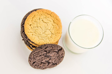 chocolate and sugar cookies stacked with glass of milk