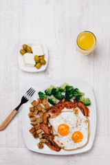 Fried Eggs on a plate with bacon, croûtons and broccoli