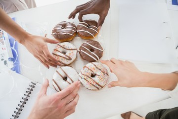 Business people taking doughnut at desk