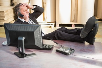 Warehouse manager using telephone at desk