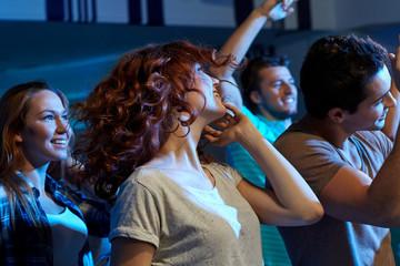 happy friends dancing at night club
