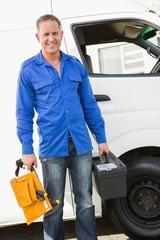 Handyman smiling at camera holding toolbox