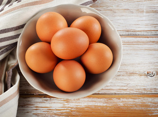 Raw brown eggs in a bowl.