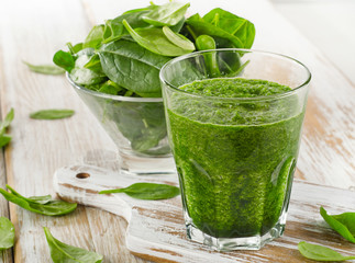 spinach smoothie in glass on a wooden background