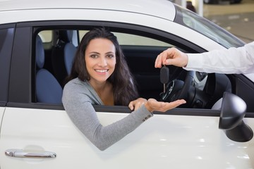 Salesman giving keys to a smiling woman