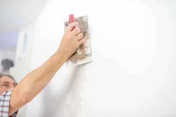 Man plastering a white wall