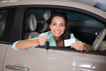 Smiling woman holding car key and business card
