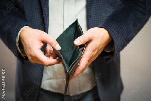 Bankruptcy - Business Person holding an empty wallet - 78319080
